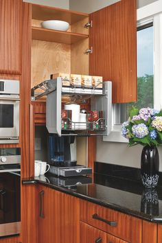 Can't reach the items you've stored in your upper kitchen cabinets? A pull-down shelf is the perfect solution; in this space, it makes coffee and tea supplies easily accessible.