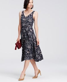 "Best in bloom: an etched floral print adds undeniable allure to this belted beauty, culminating in a flowy side slit skirt. V-neck. Sleeveless. Self tie belt. Front side slit. Lined bodice. 28"" from natural waist."