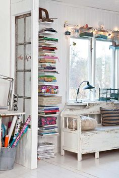 wall mounted shelving for stacks of magazines. Vintage/recycled window installed adds character.