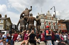 Fans relax next to the iconic Champions Sculpture on Green Street before last weekend's game at Upton Park - the statue honours the club's stars of the 1966 World Cup final - Bobby Moore, Geoff Hurst and Martin Peters, plus Ray Wilson helping hold Moore aloft