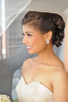 Natural tones were used to keep the bride's makeup simple and acentuate the bride's glowing tan. For the hair, the bride's dark brown locks was styled to a romantic french twist with petal accents. | www.BridalBook.ph