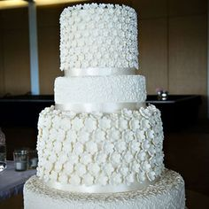 The stunning wedding cake had four tiers and 900 hand made flowers featured throughout. It was made by the bride's mother.  Wedding cake:Ruth's Wedding Cakes