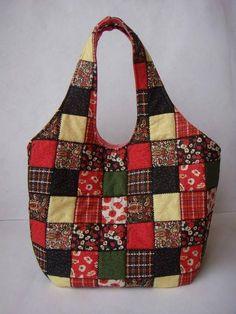 Bolsa confeccionada em tecido padrão patchwork, estruturada com manta acrílica. Bag made of standard patchwork fabric, structured with acrylic blanket, embroidered with stitching, lined with plain f