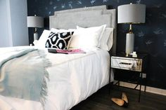 Chic contemporary bedroom is fitted with a light gray art deco headboard placed against a blue bird print wallpapered wall and supporting a bed dressed in gray border bedding accented with matching shams, blue and black ikat pillow, and a pale blue fringe throw.