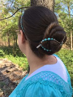 Turquoise flexi clip holding her very long hair in a bun, turquoise hairband, turquoise shirt- this lady knows how to co-ordinate!
