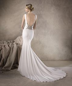 Wonderful mermaid wedding dress crafted entirely in crepe. A dress that hugs the body and culminates in a discreet bateau neckline and draws the eye to the beaded appliqué adorning the base of the low back. La Sposa Wedding Dresses, Slit Wedding Dress, Elegant Wedding Dress, Designer Wedding Dresses, Bridal Gowns, Bridesmaid Dresses, Fashion Group, Wedding Dress Crafts, Pronovias