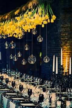 Upside down yellow flowers, with floating candles for chandelier, with black and white table decor