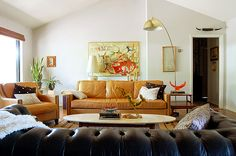 Beautiful tan leather couch, beautiful dark shesterfield, cool arching lamp, light color scheme