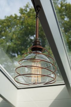 One of 7 pendants in a conservatory, made with brass lamp holders, various copper and brass fittings and copper wire.