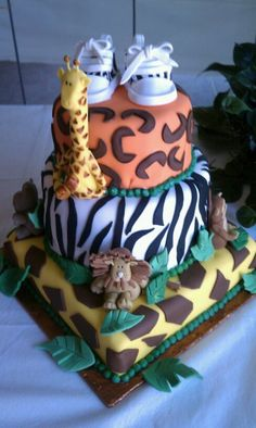 - 3 Tier jungle theme baby shower. Rolled fondant to match zebra, giraffe and cheetah prints. All animals I made out of fondant. Zebra print sneakers are a frosting sheet with the zebra print placed on the fondant before assembly