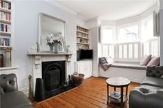 window seat, shutters, white lounge, wooden floorboards, nice fireplace - love this lounge