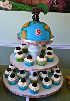 Little Big Planet Cake and cupcakes. Cupcakes are topped with Sackboy head made out of chocolate.