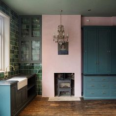 Pink walls in a kitchen with contrasting dark blue kitchen units and green tiles. The antique chandelier and vintage oil painting look unexpected in a kitchen.