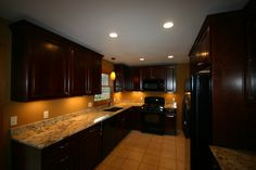 Kitchen Remodel with dark cabinetry, granite countertops with under cabinet lighting, tile flooring, under mounted sink, upper cabinets with crown molding.