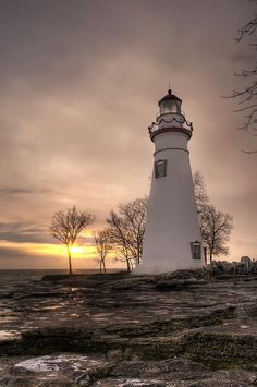 """""""Winter Sunrise at Marblehead Lighthouse - Portrait"""" - The lighthouse at Marblehead Point on Lake Erie in Ohio. I took another ride out to Marblehead to try to catch the sunrise. Right around the winter soltice the sun rises behind the lighthouse as taken from the rocks. It was cold and the rocks were very icy. I almost took a spill a couple of times. Its a good thing I didn't because unlike in the summer time there was absolutely no one else around."""