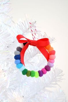 Get the kids to make these cute pom pom Christmas decorations - so colorful they look so good on a White Christmas tree!