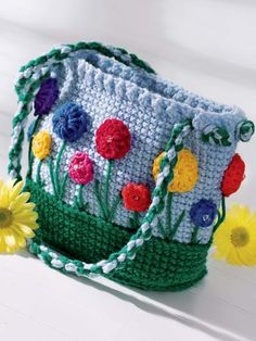 """Bright springtime flowers are appliqued onto this fun purse, perfect for any little girl to tote around.Size: 7""""W x 7""""H x 3""""D. Made with medium (worsted) weight yarn and size G/6/4mm hook.Skill Level: Easy"""