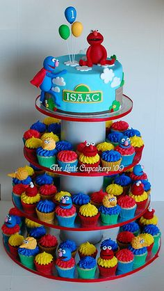 An idea if I ever have to make a sesame street cake...  Love the idea of having a small cake on top and mini cupcakes on tiers below