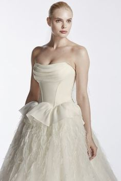 Complete the modern fairy tale wedding of your dreams in this enchantingly romantic feather skirt ball gown!  Strapless bodice features a draped organza neckline and alluring corset detail to define and shape the waistline.  Full, organza ball gown skirt is glamorously decorated with soft feathers for a luxurious, ultra-feminine bridal