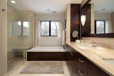 Lazienka projekt #6886. Nowoczesne wnętrze zaskakuje luksusowymi rozwiązaniami. Pod oknem zamontowano niską, dużą wannę z ciemnym, drewnianym obiciem. Również szafki na jednej ze ścian wykonano z brązowego drewna, co z beżowymi kafelkami i marmurowym blatem daje elegancki efekt.