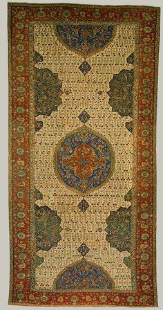 Medallion Ushak carpet, early 17th C: Ottoman Western Anatolia, Ushak region. Medallion Ushak carpets usually have a red or blue field decorated with a floral trellis or leaf tendrils, central medallions and a border containing palmettes on a floral and leaf scroll, and pseudo-kufic characters. This example is partially restored, a typical white-ground field pattern is combined with the Medallion Ushak.