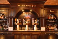 "Bismarck, ND - The Blarney Stone Pub. A dark wood bar and tables and flat-screen TVs accent this long narrow space in downtown Bismarck. You'll find dozens of pints and bottled beers, including a handful of Irish brews, plus ""married pints"" that mix two ales. Appetizers include the usual mix of bar offerings, given cheesy Irish-influenced names (Irish nachos, Celtic crab cakes, Mussels Malone)."
