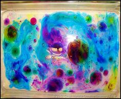 """Water in a bin.  Slowly add drips of paint (which floats on top of the water)  Place paper on top, which absorbs the paint, then gently remove.  """"Paper Marbling"""""""
