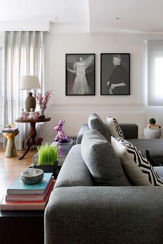 Apartamento moderno, decoração da sala de estar com sofá cinza, adornos e quadros em preto e branco.
