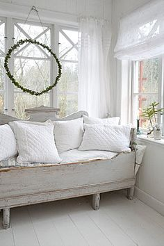 Simple Swedish wooden faded painted daybed piled high with white vintage fabric cushions