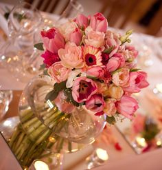 spring wedding flowers fish bowl vase centrepiece of tulips, gerberas and lisianthus, in pastel and raspberry pinks. For more wedding flowers ideas please visit http://www.thefineflowerscompany.co.uk