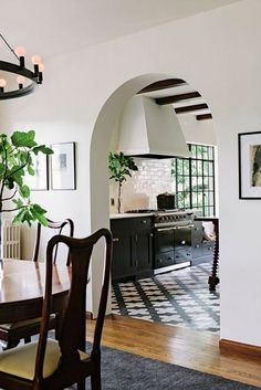 Arch doorway into kitchen with printed tile floors, exposed ceiling beams, and black cabinets.