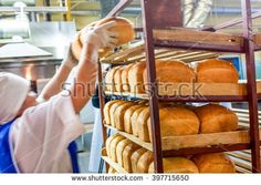 factory worker puts bread on the shelves Factory Worker, Industrial, Shelves, Bread, Food, Shelving, Shelving Racks, Industrial Music, Breads