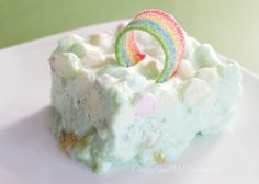St. Patricks Day Green Dream Jello Salad...made with lime jello, cool whip, cream cheese, marshmallows, and fruit cocktail (and a candy rainbow on top!)