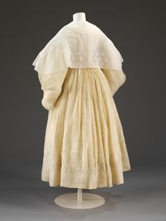Wedding dress 1834 Wedding dress consisting of a pelisse robe with large imbecile sleeves and bell shaped skirt. It is made of white muslin with self coloured cotton embroidery in a formal floral pattern.