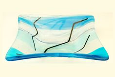 A square bowl in blue, white and transparent stripes fused on a transparent base with black zig-zag string pattern.  Approx size 20cm by 20cm by 5cm