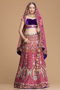 Indulge in this graceful red net lehenga with a silk and velvet blouse and net dupatta. The net lehenga is tailored with satin and brocade lining, aesthetically pleasing resham and stone work adds grace. The blouse again has embellishments all over.