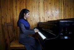 Una pianista segue una lezione all'istituto nazionale afgano di musica, a Kabul. La ragazza fa parte di un'orchestra composta da trentacinque donne. - Ahmad Masood, Reuters/Contrasto