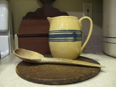 Yellow ware pitcher with early wooden spoon.