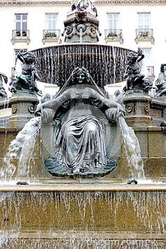 This is an image of a a fountain in Nantes, France with a statue of a female goddess pouring water from two water pots could be the Roman Venus or the Greek Aphrodite portraying abundance. She is flanked by small cubit angels. Aphrodite, Venus, Fountain, Female, Abundance, Switzerland, Roman, Pots, Greek