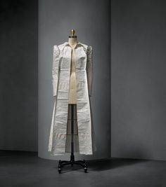 Maison Margiela (French, founded 1988), Martin Margiela (Belgian, born 1957). Coat, autumn/winter 1998–99, Semi–Couture. White Tyvek printed with pattern–drafting–paper motifs, seams hand–lapped with adhesive tape. Photo © Nicholas Alan Cope. #ManusxMachina #CostumeInstitute