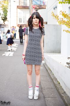We met Sayaka, a cutely-styled 20 year-old-girl, in Harajuku. The pink streak in her hair is what first caught our eye. She was wearing twin tails and a monochrome mini dress. Her holographic backpack, pink heart choker, and jewelry are from Spinns. Her cute holographic platform sandals are by the girlie Japanese brand Liz Lisa. (Tokyo Fashion, 2014)
