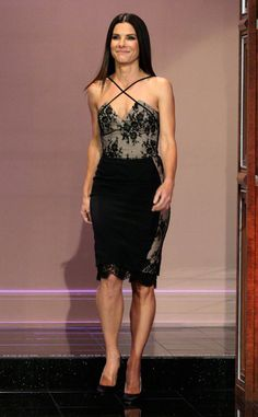 Sandra Bullock promoted The Heat on The Tonight Show with Jay Leno wearing a sexy black-and-nude lace cocktail dress by Azzaro.
