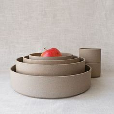 Designed by Los Angeles-based Taku Shinomoto and made in Japan. The Hasami series of stackable dinnerware can also be used as modular containers. Each piece is kiln-fired without glaze, leaving the surface feeling similar to terracotta.  Use the bowls and plates as is, or pair them together to form a handsome covered bowl. The larger pieces may also be used as serving trays/dishes or as fruit bowls.
