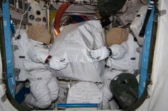 ISS Expedition 40 (1 Aug. 2014) --- Two unoccupied Extravehicular Mobility Unit (EMU) spacesuits, photographed by an Expedition 40 crew member, appear to hold stowage containers in the Quest airlock of the International Space Station.