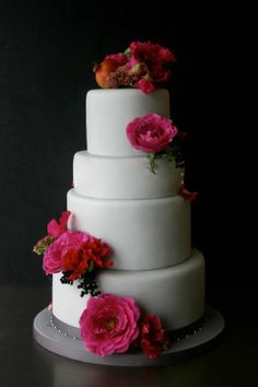 Pink and red flowers on wedding cake by Sugarplum Cake Shop