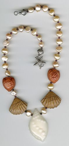 Beautiful complimentary colors in this carved seasheel and fish necklace. The pearls are a lustrous peach color, with alternating garnets. The focal bead is a carved conch shell of jade and the scallop shell and fish are agate. Sterling silver scallop shell beads at the ends.Wear your last trip to the beach! The focal bead measures 50 x 30mm, the scallop shells are 20mm, the fish are 18mm, the pearls are 9mm and the garnets are 4mm. Total length is 20 inches.