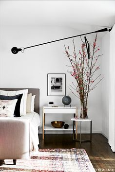 Neutral bedroom with branches, modern lighting, and white side table with alarm clock