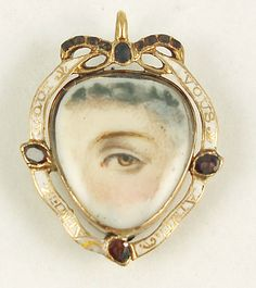 """Eye miniature, circa 1790. Brown eye and curls. Heart-shaped frame with garnet bow and three garnets set in white enamel band, saying """"Aimez Qui Vous Aime."""" ©2007 Cathy Gordon, Olympus Imaging Corp."""