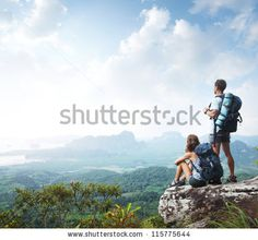Hikers with backpacks enjoying valley view from top of a mountain by Dudarev Mikhail, via Shutterstock