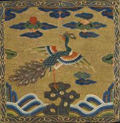"""A very rare embroidered civil official's 'Peacock' rank badge, """"buzi"""" if the Qing Dynasty Kangxi period (circa 1662-1722). Made for a 3rd rank official, finely embroidered in satin stitch, the centre with a peacock, standing with one leg raised and the other standing on rockwork, its head turned towards the sun amidst ruyi-form clouds, against a ground of couched gold thread, above rolling waves, bordered by a narrow band of classic scrolls 10 1/4 in. (26 cm.) square."""